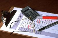 Bookkeeping records kept by hand before accounting software. Picture of pencil, paper and calculator.